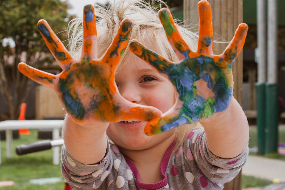 kid with paint in her hands